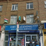 Exterior of flat above dry cleaning and ironing shop next to bus stop