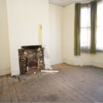 Empty room with fireplace and window with green curtains and dark wood flooring