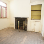 Empty room with dark wood flooring, fireplace and window