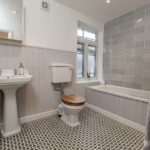 Tiled big pewter bathroom with mirror, sink, toilet and bath