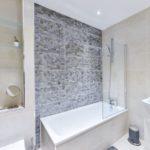 Tiled bathroom with grey centrepiece wall and bathtub