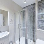 Modern tiled bright bathroom with grey wall, shower and mirrored cabinet