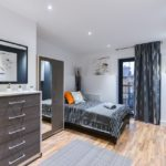 Dark grey and white bedroom with orange cushions and laminated flooring with striped bedsheets