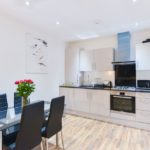 Bright kitchen and dining area with glass table and flowers