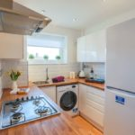 White bright kitchen with wooden worktop surfaces with yellow flowers, a fridge, a hob and a washing machine
