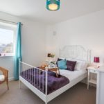 Big bright white bedroom with blue curtains and purple throw on bed.Chair in corner with side table too