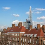 View of the Shard in blue sky from the flat looking over brick houses with red roofs