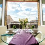 Glass dining table with view to outside through open double doors. Blue sky and purple table runner.