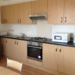 Wood kitchen counters with fridge, microwave and kettle. A dining table too.