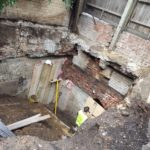 Outside with hole in ground, exposed brick and builder in hi-vis jacket next to some foliage