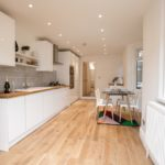 Long white kitchen with laminated flooring, window and table set for four