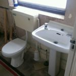 Bathroom in progress with white toilet and sink with no carpet or wallpaper or paint. Pieces of wood scattered.