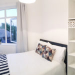 White bedroom with double bed and large window with striped throw and bookcase